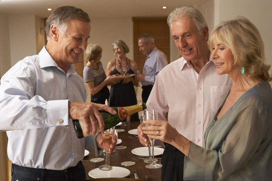 Image: Man Serving Champagne to Guests at Dinner Party