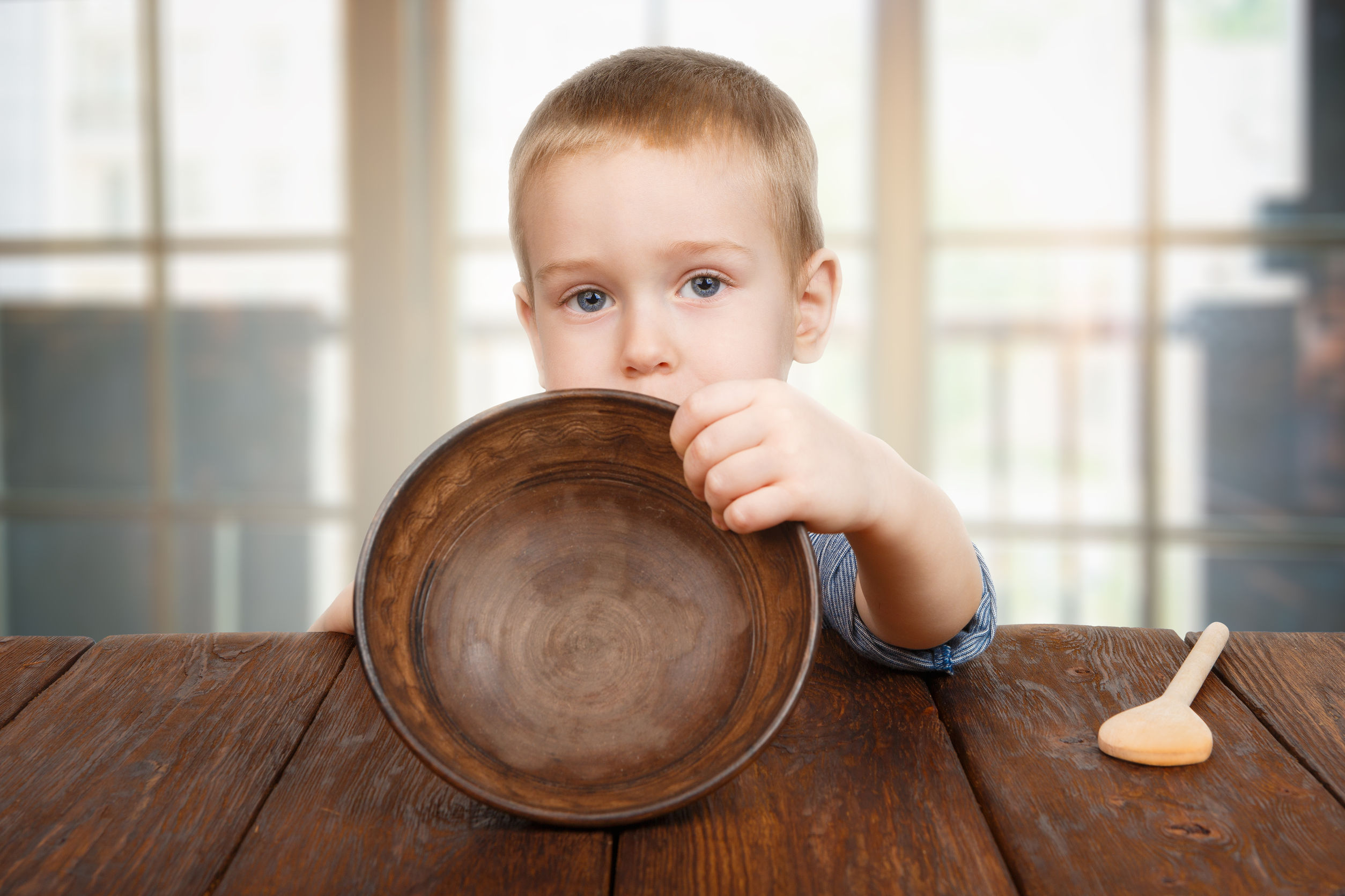 38229290 - cute small child boy sitting at wooden table shows empty plate
