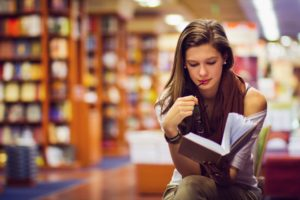 teen reading in a library