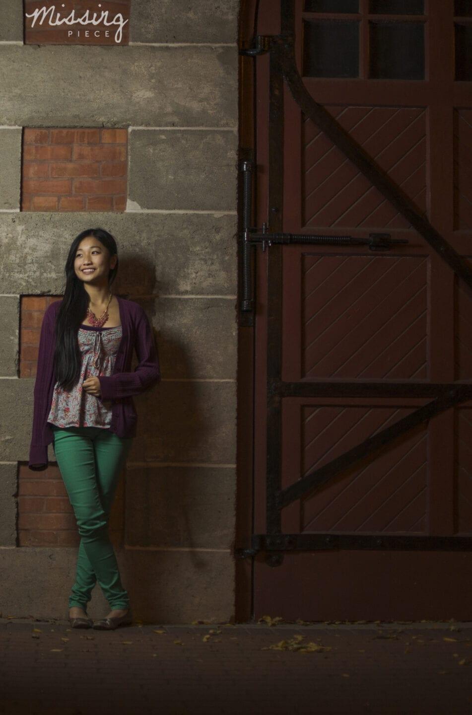 Girl posing for a portrait at whyte avenue in Edmotnon beside a barn door