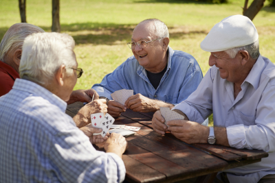 group of four elderly men having fun and playing cards game