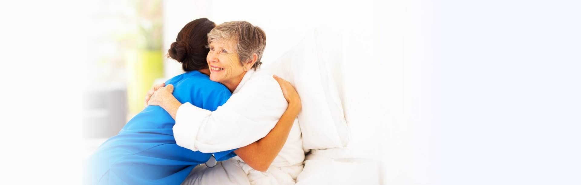 nurse hugging a senior woman on a bed