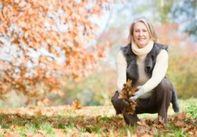 senior-woman-collecting-autumn-leaves-on-walk_syhgs9xcbo