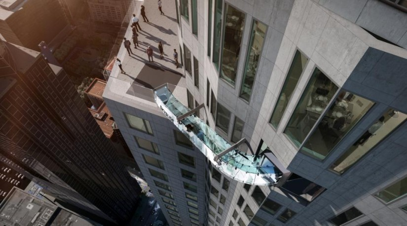 This undated artist's rendering provided by Overseas Union Enterprise Limited shows a glass slide 1,000 feet above the ground off the side of the U.S. Bank Tower in downtown Los Angeles. The 45-foot-long attraction is part of a $50 million renovation that will also put a bar and open-air observation deck on the top floors of the 72-story building. (Michael Ludvik/OUE Ltd. via AP)