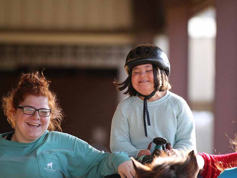 girl with black helmet on horseback with woman with red hair next to her