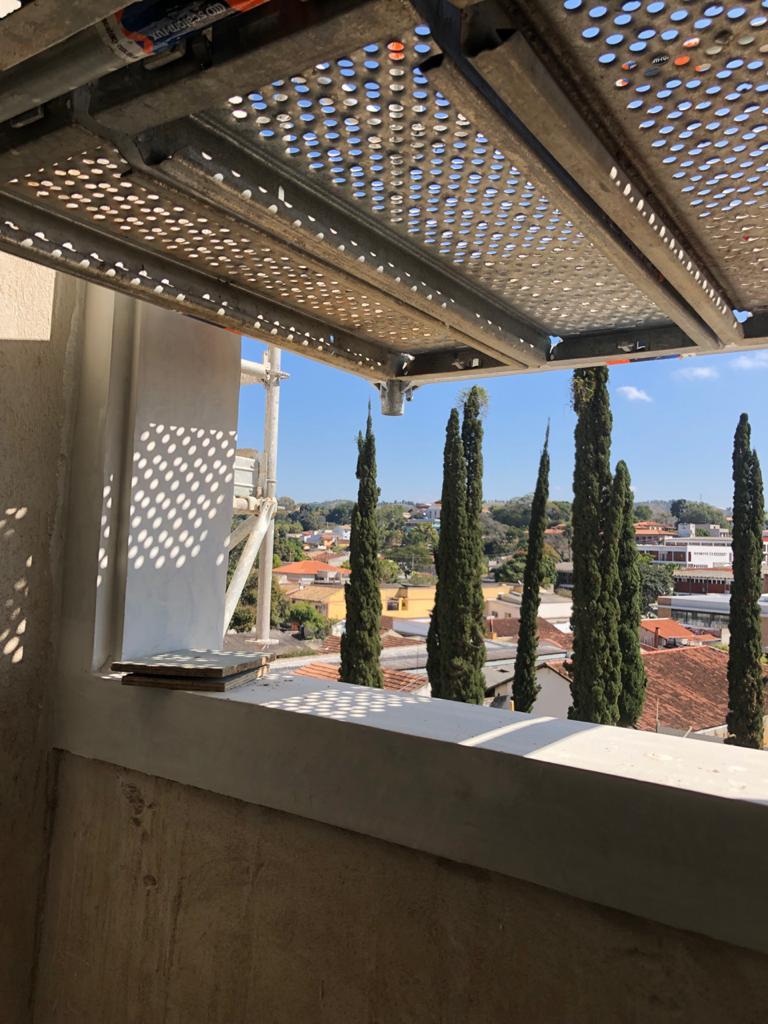 Da janela, veem-se as árvores do jardim e a cidade de Vassouras