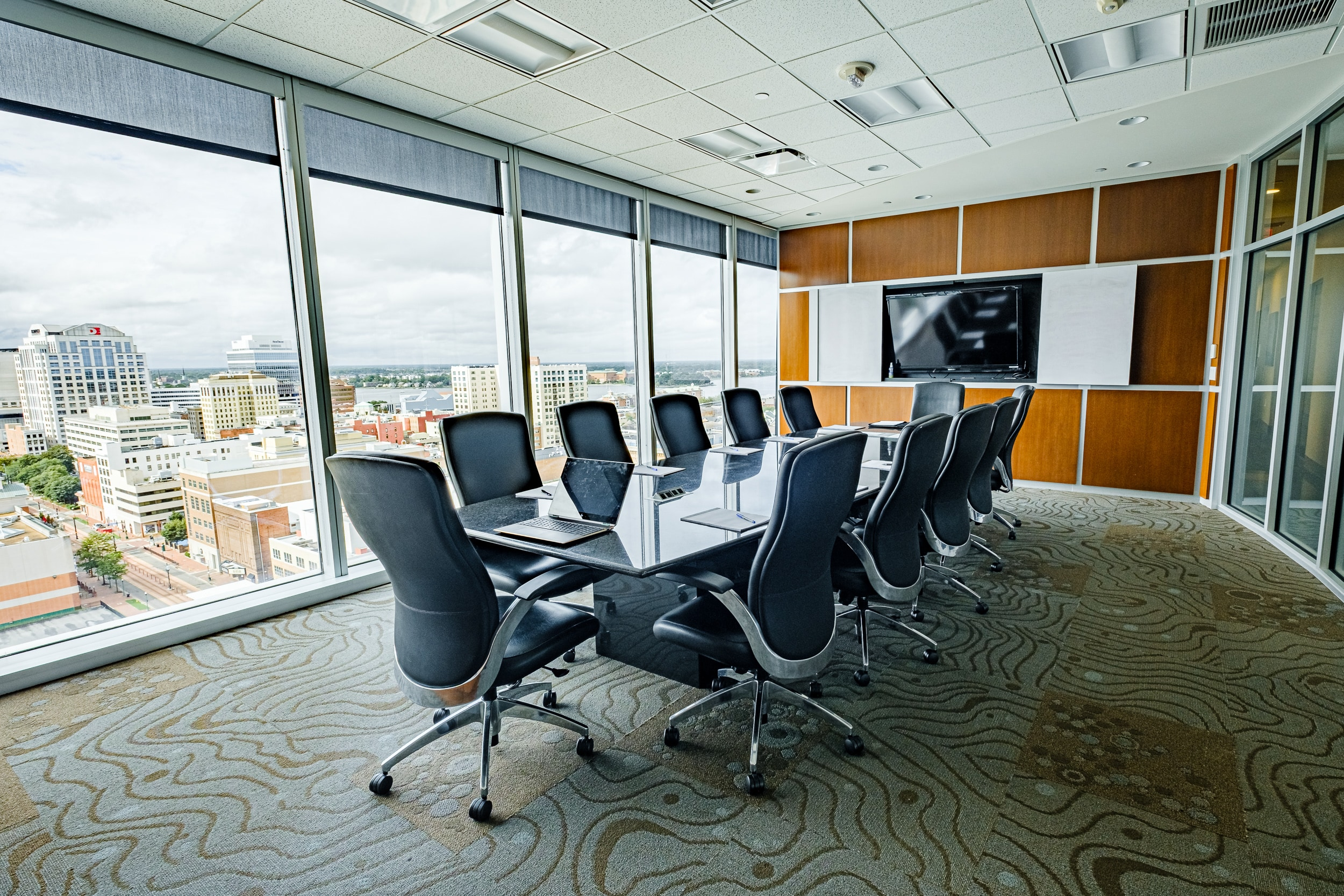 OSS Conference Room Wells Fargo Center. Full room view; displaying glass wall with beautiful view, modern decor and audio/visual wall.