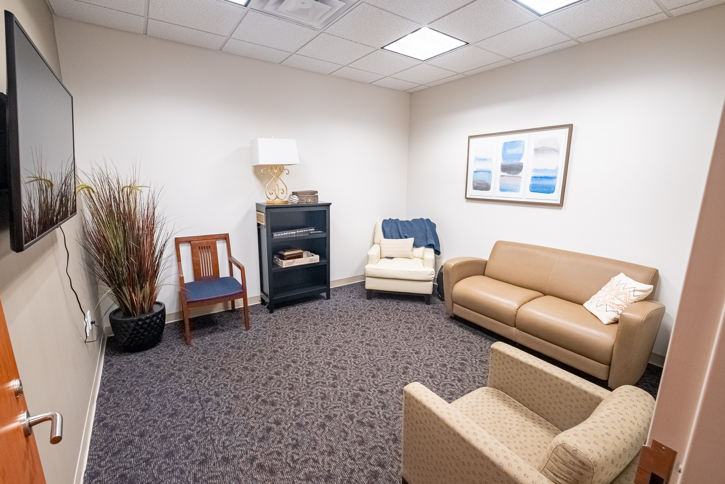 OSS Headquarters Waiting Room. Comfortable looking room with various seating, plant, TV and reading material shelf.