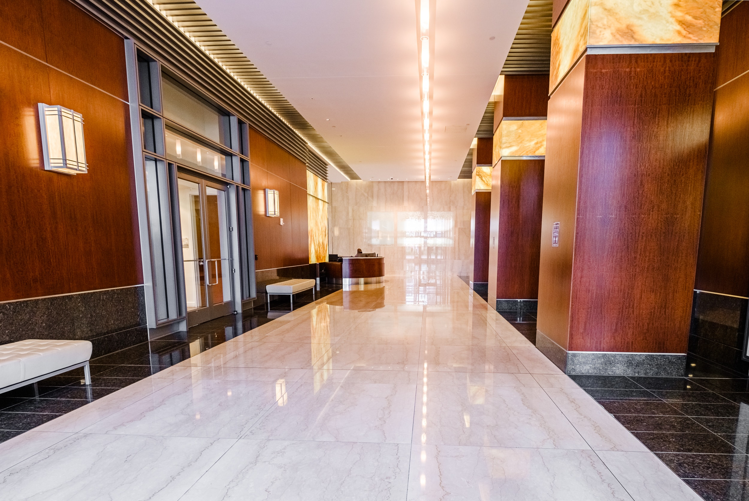 OSS Wells Fargo Center Lobby. Large and brightly-lit main lobby of building with stone floors and modern decor.