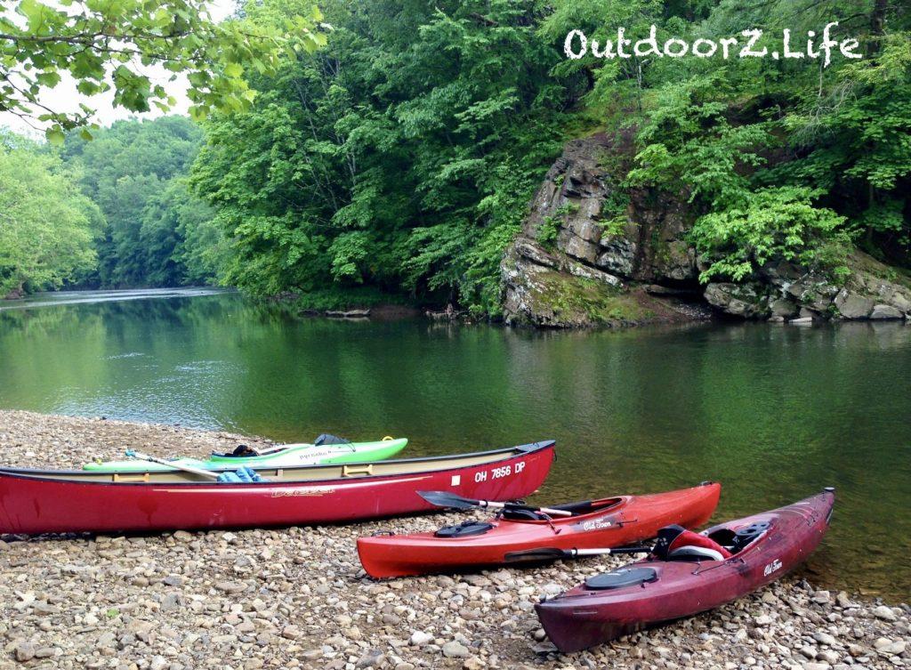 Canoe and kayaks on a river bank