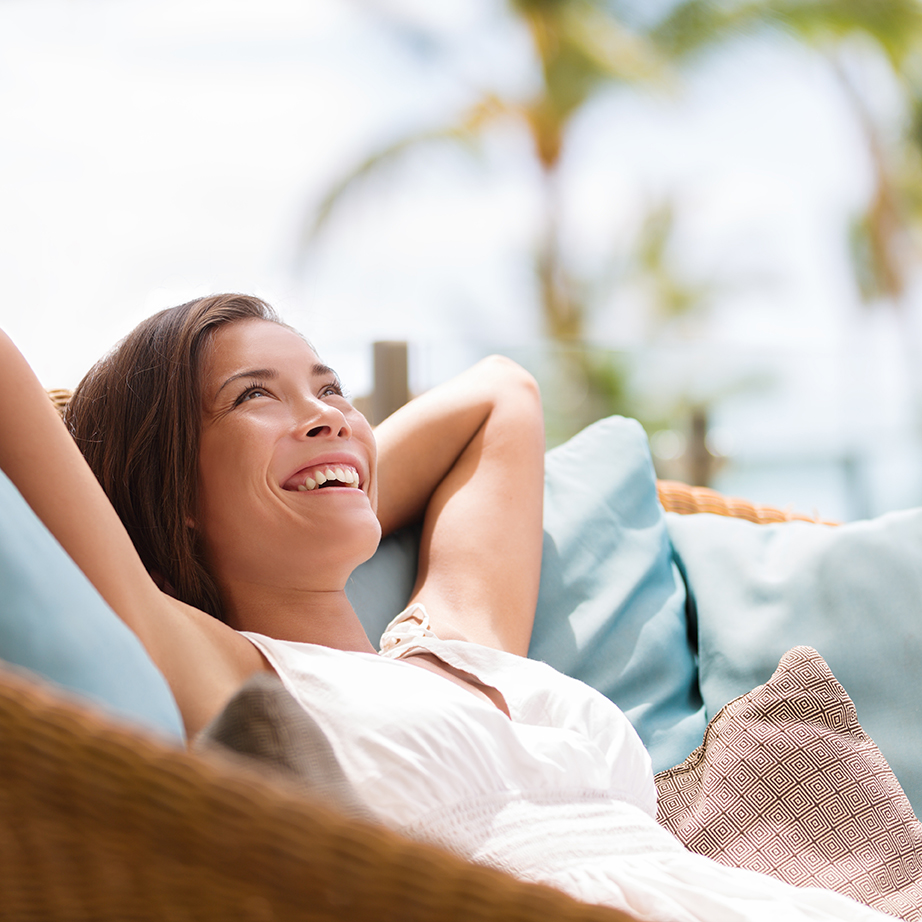woman relaxing on outdoor sofa daydreaming