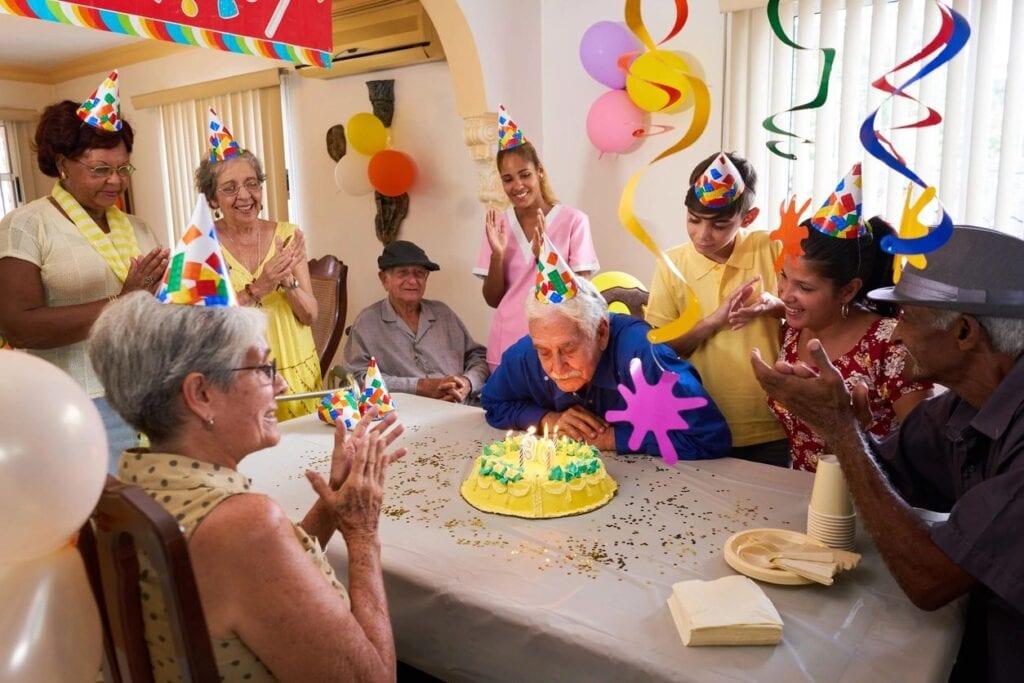 An elderly man celebrating his birthday with his senior friends