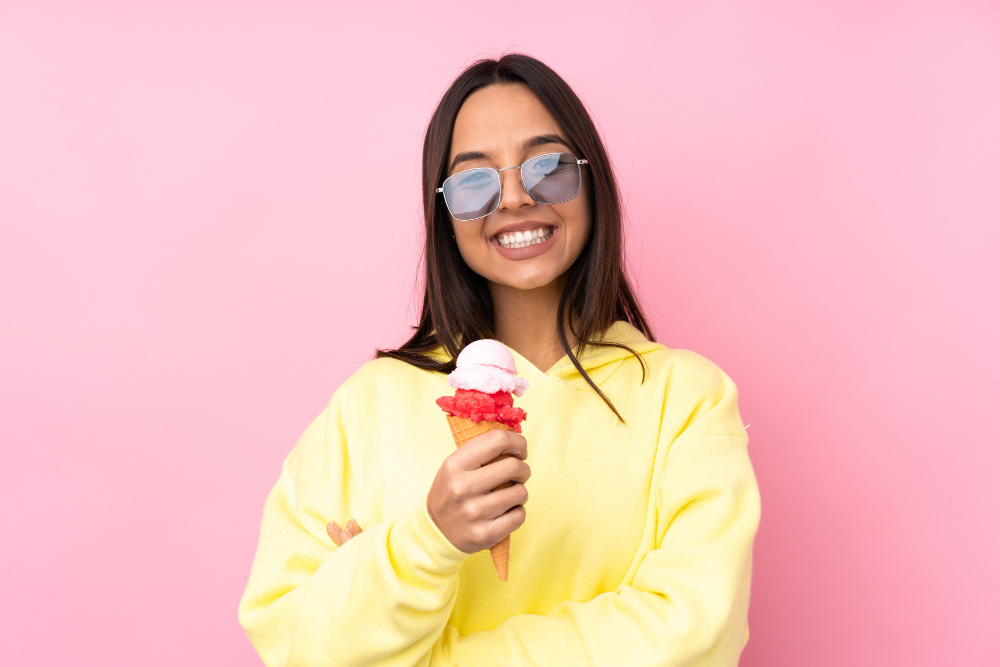 young-brunette-woman-holding-cornet-ice-cream-isolated-pink-looking-up-while-smiling
