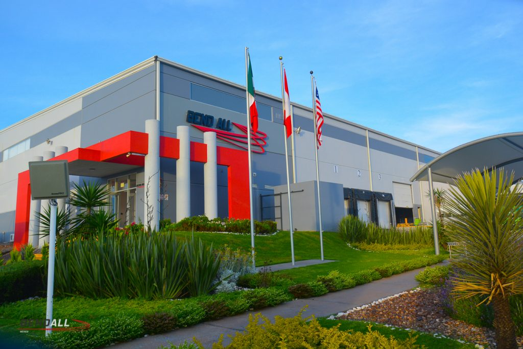 This is the front door of the building of the Mexico Bend All Plant. It is a grey and red building. It also has the flags of Canada, Mexico and the United States of America out front. There is a bus stop and well-landscaped green lawns.