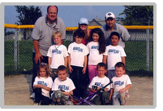This is a picture of a baseball team that Bend All has sponsored . The children are in white t-shirts with multi-coloured pants. Four of the children are kneeling, four are standing. There are three adults in the back.