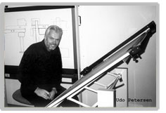Udo Petersen is sitting in front of a drafting table wearing an all black outfit.