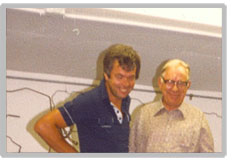 A picture of both Horst Udo Petersen and Horst Mueller. One is a brunette wearing a short sleeve navy blue polo top with a white button placket. The older gentleman is wearing a cream long sleeve shirt with buttons. He has glasses and white hair.