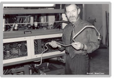Horst Mueller poses in a black and white holding up a coolant hose.