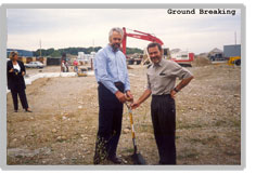 Horst Mueller and Udo Petersen are both holding a shovel while participating in a groundbreaking ceremony . There is a blond woman wearing in a black and white outfit.