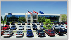 A parking lot full of cars in front of a concrete and glass building. Three flags are in the center, Canada, Mexico and the United States