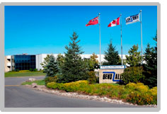 Entrance to Bend-All Automotive in Ayr, Ontario. There are 3 flags in the foreground as well as the Bend-All sign. The building itself is in the background.