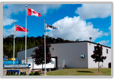 Entrance of the Bend-All Plant in Ayr Ontario. There are three flags and a truck trailer in the picture on the left. Two trees are in the foreground.