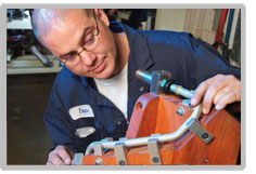 A bald man with glasses inspects a prototype for heating and cooling.