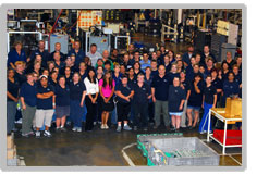 A group of floor employees on the shop floor. There is a sea of navy shirts with a pink tshirt and a white tshirt on the left.