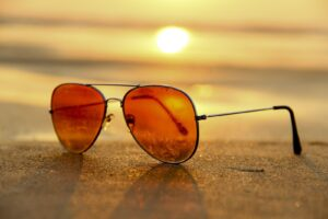 a pair of sunglasses laying on the beach