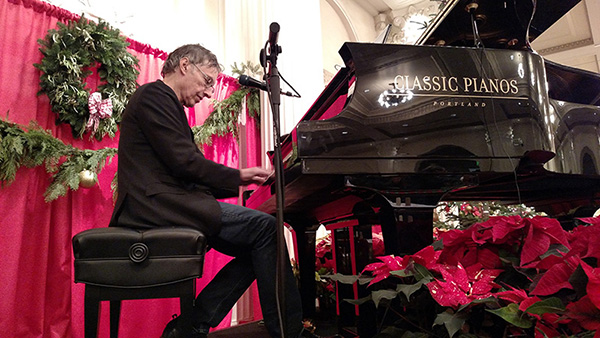 picture of Tom Grant donating his time and  playing piano on a stage for the homeless christmas dinner