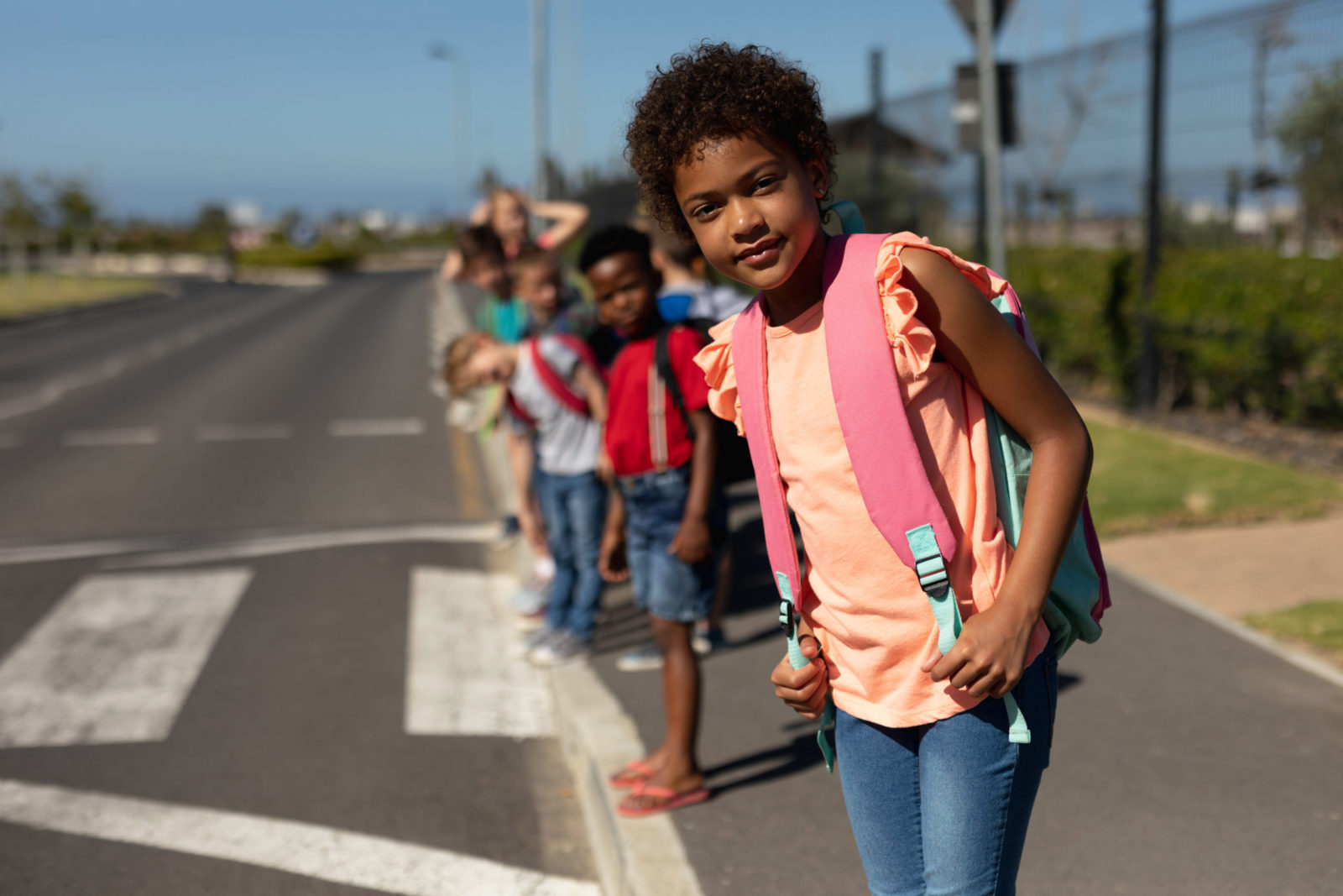 girl waiting for bus at crosswalk