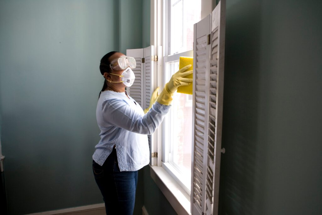 Domestic worker cleans windows