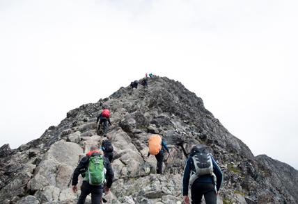 multiple climbers hiking up mountain