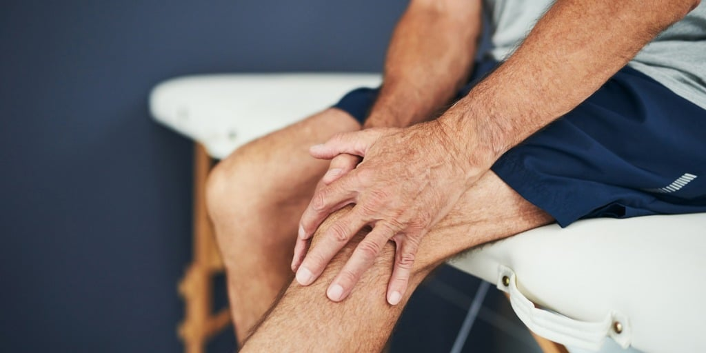 Male patient holding knee cap experiencing pain