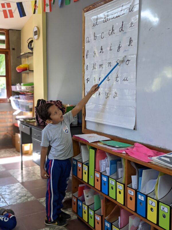 student pointing to alphabet chart