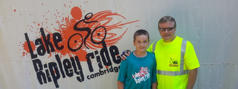 father and son in front of ripley ride sign