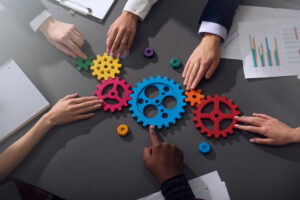 Photo of Teamwork of businesspeople work together and combine pieces of gears. Partnership and integration concept