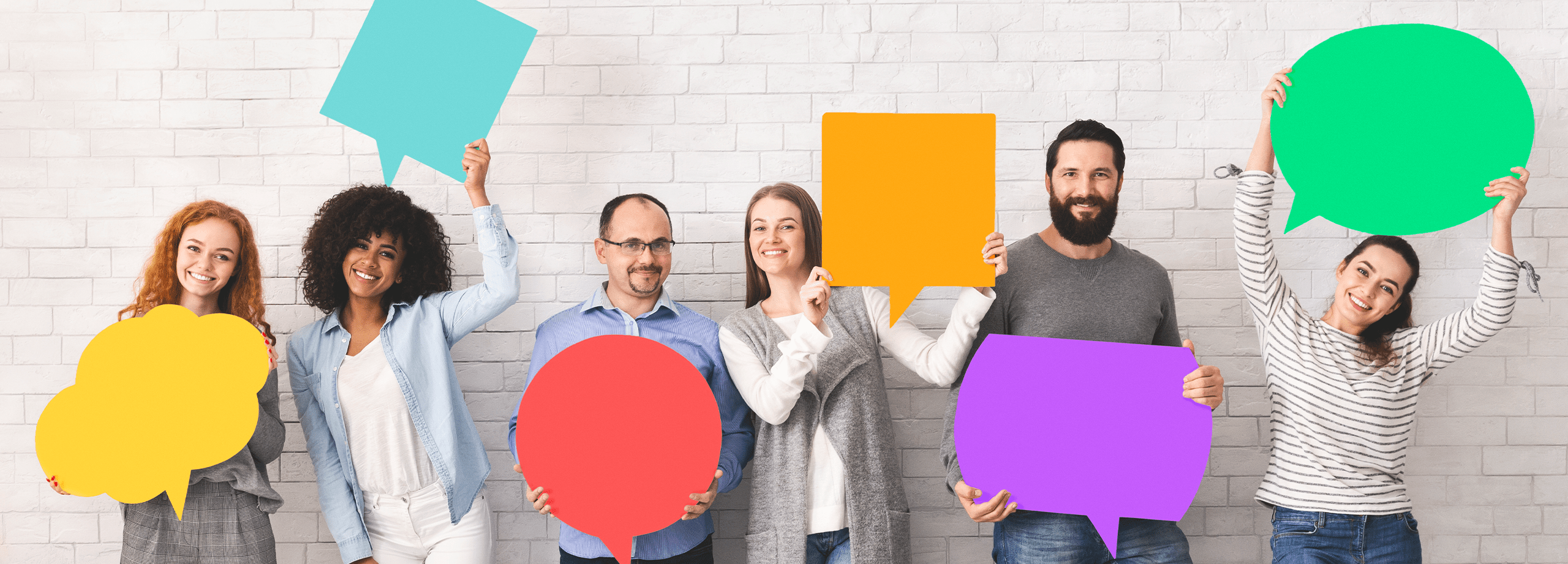 Photo of a variety of adults holding speech bubbles.