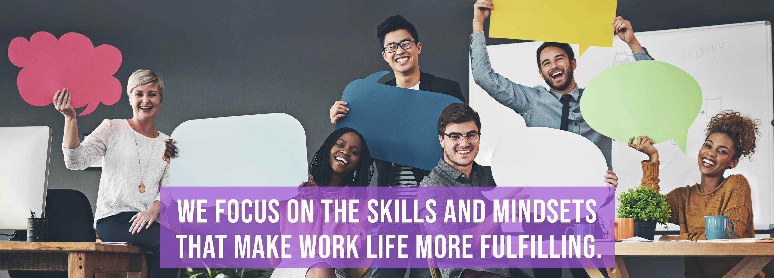 "Photo of a group of professional adults holding speech bubbles with the tagline ""We Focus On The Skills And Mindsets That Make Life More Fulfilling."""