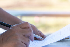 a hand holding a pen and paper.