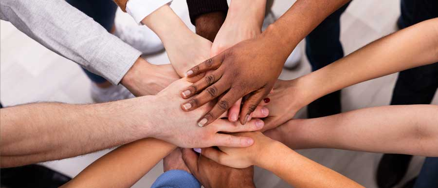 peoples hands on top of each other of all races   views on social justice