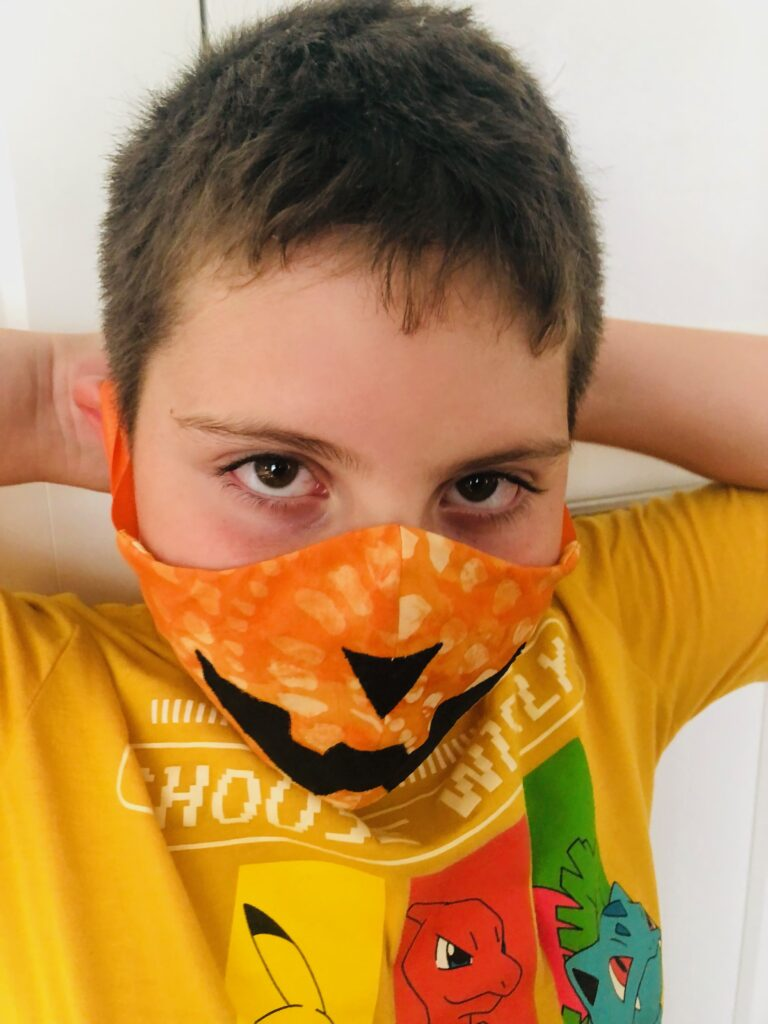 kid wearing costume face mask