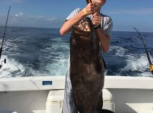 Aaron Hanania lifts the 80 pound Grouper he caught while deep sea fishing outside of Cozumel, Mexico