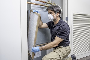HVAC tech wearing mask and gloves changing an air filter