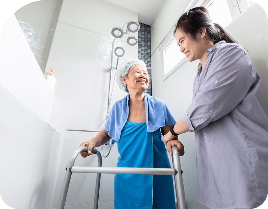 Woman helping elderly woman with bathroom medical equipment and supplies