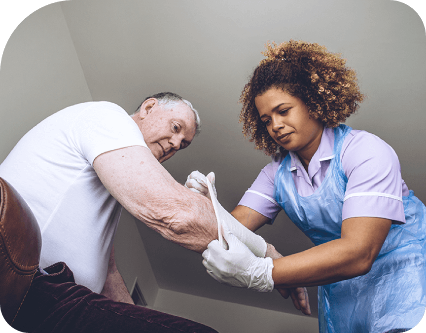 Healthcare worker bandaging a man's arm wound