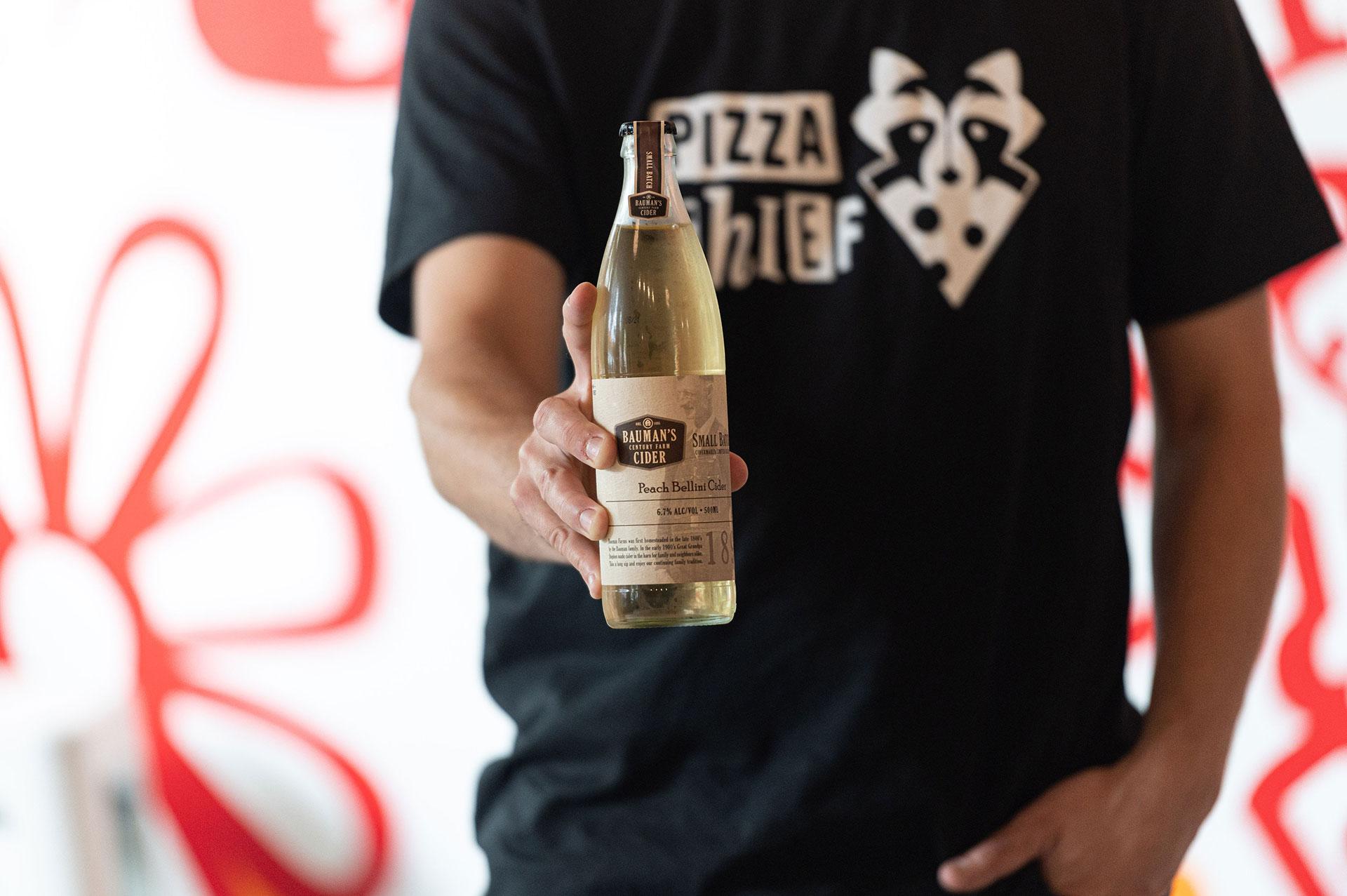 pizza-thief-waiter-holding-cider-bottle