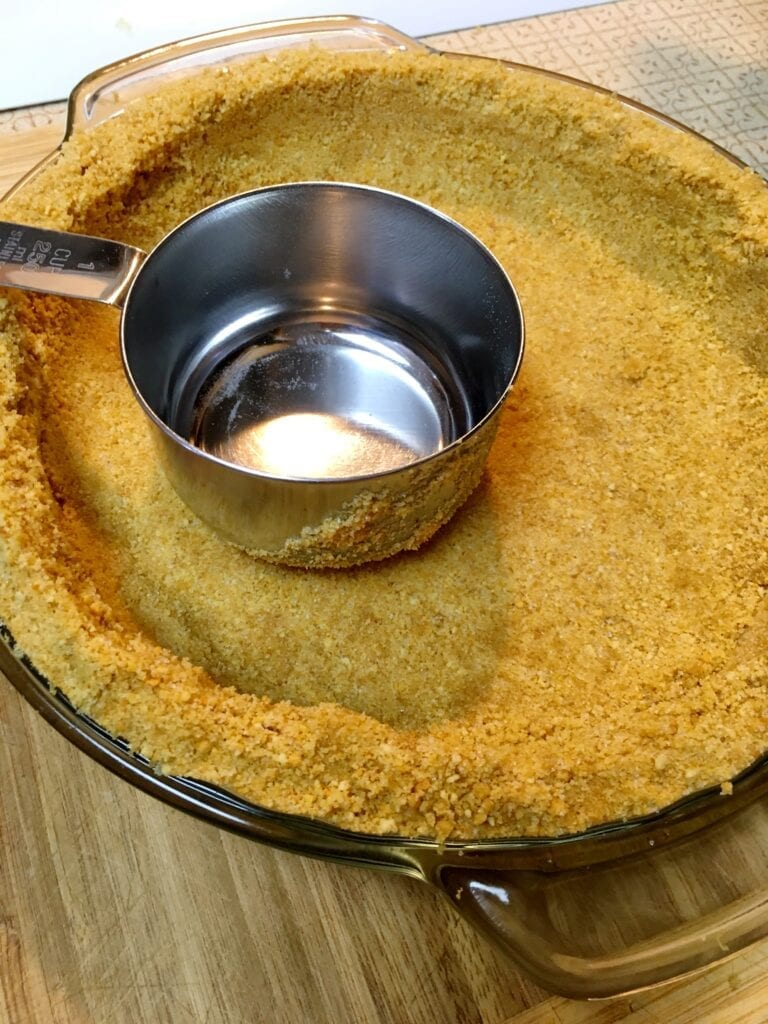 Using a Measuring Cup to Press in the Graham Cracker Crust