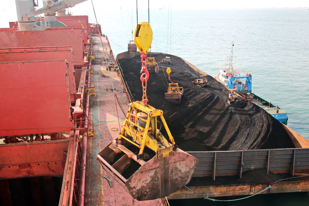 Ivan Kuzkin Loading coal from cargo barges onto a bulk carrier using ship cranes and grabs at the port of Samarinda, Indonesia.