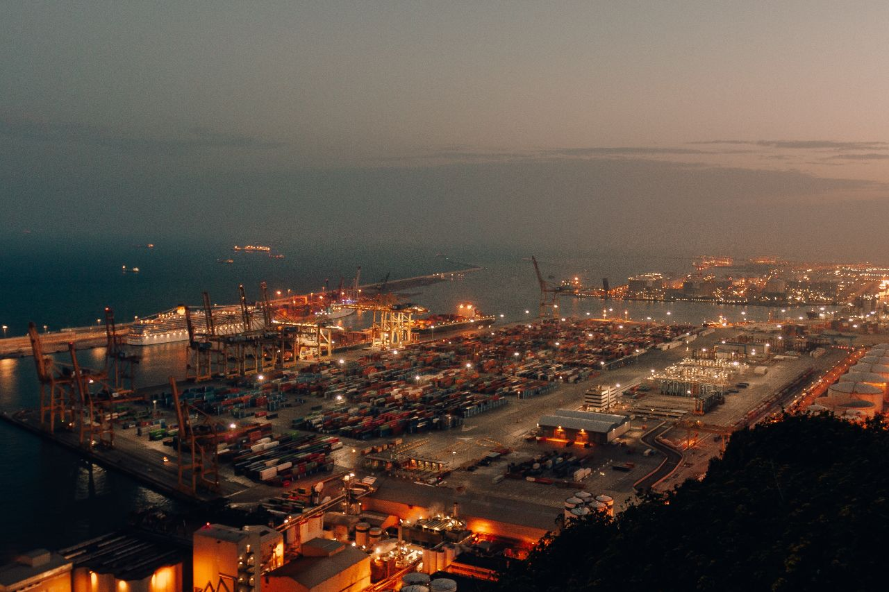 distant-shot-of-a-port-with-boats-loaded-with-cargo-and-shipment-during-nighttime (1)